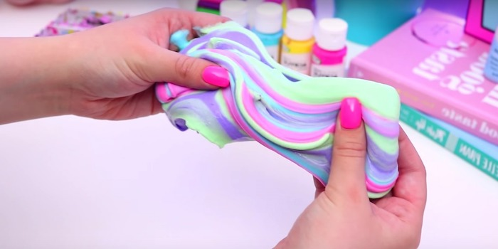 fluffy slime recipe, two hands with hot pink nail polish, kneading a piece of multicolored goo, in pastel colors, minty green and pale purple, pink and blue