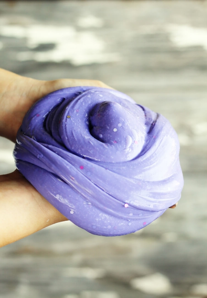 hands holding a large piece of fluffy slime, glossy and smooth, with pink and silver glitter, shaped into a round pile