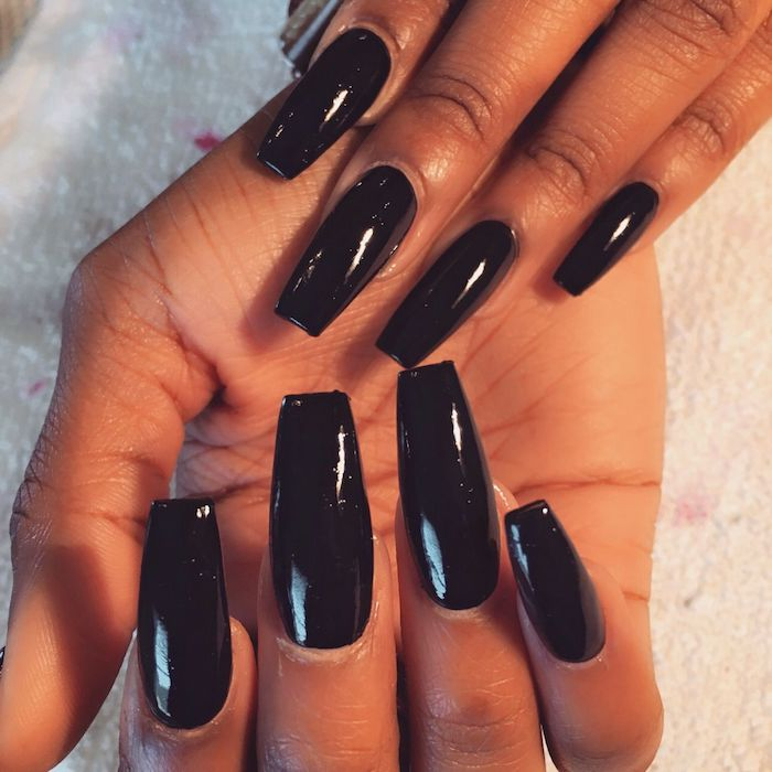 black smooth and glossy nail polish, on long squoval nails, attached to a pair of brown hands, resting on a towel-like fabric