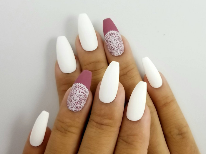 two hands with four visible fingers, and coffin shaped nails, three painted in matte white, and two in matte rose ash pink, with a white lace pattern