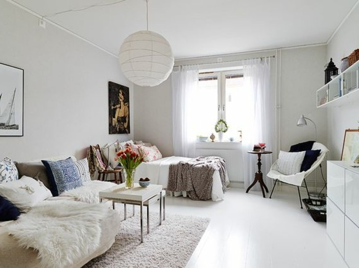 smooth white floor, inside a bright room, with a bed and a window, a corner sofa with lots of cushions, some bookshelves and cupboards