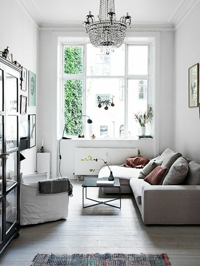 crystal chandelier inside a white room, with a large window, and a pale beige corner sofa, simple living room designs, black coffee table, and a white armchair