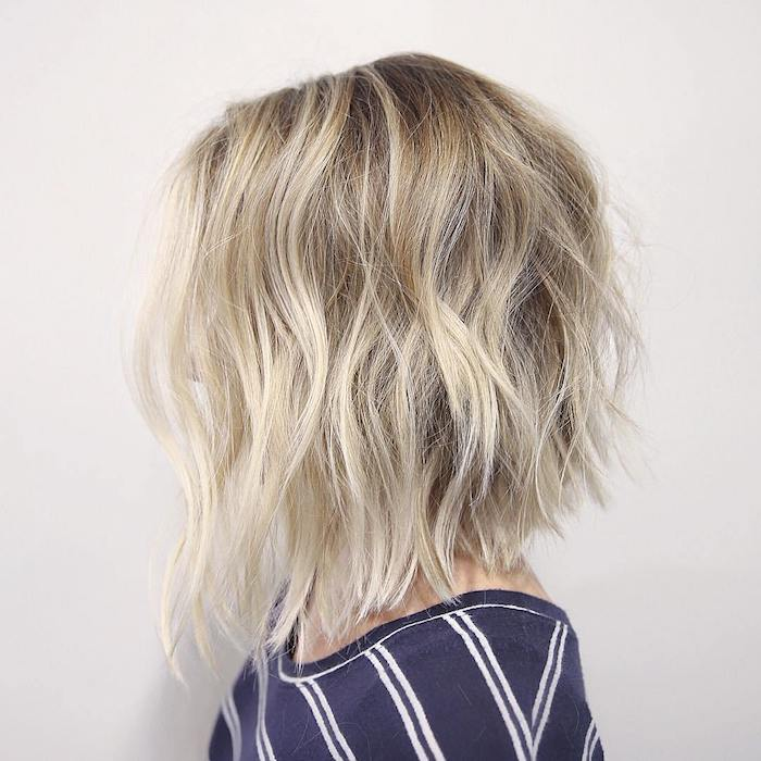 soft platinum blonde waves, on hair with dark ash blonde roots, hairstyles for women with thin hair, on woman in profile, wearing a striped jumper, with hair obscuring her face