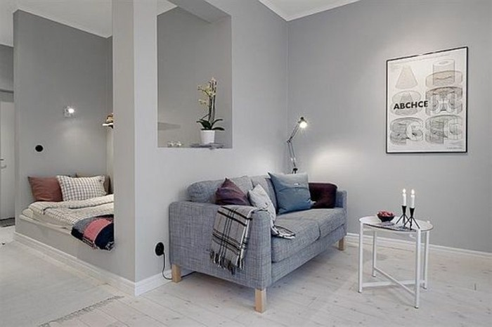 partial wall in pale grey, separating a bed and a living room area, grey modern sofa, small round coffee table, living room furniture for small spaces, framed artwork and two lamps