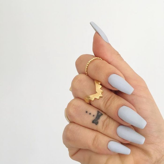 tattoo on the ring finger of a hand, wearing several golden rings, and pale creamy grey nail polish, on matte coffin nails