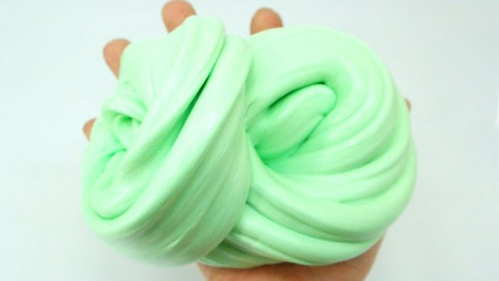 little hand holding a pile of minty green goop, twisted into a knot-like shape, fluffy slime recipe, off-white background