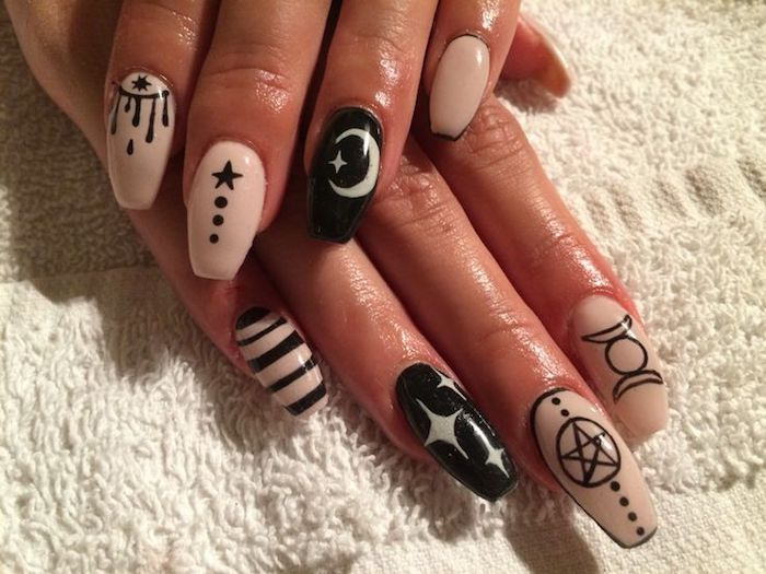 stars and stripes, moons and other shapes, on the nude pink, and black manicure of two hands, with squoval nails
