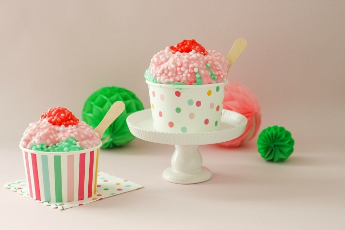 ice cream-like slime in red, green and pale pink, with small white beads, slime recipe with borax, poured into two multicolored paper cups