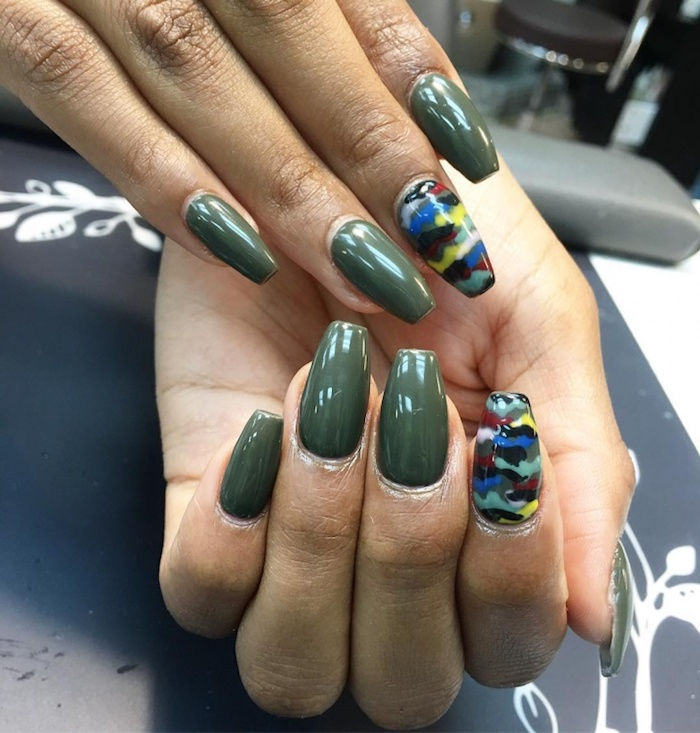 camouflage squoval nails in olive green, on a pair of tan hands, two of the nails are painted in a multicolored camouflage pattern