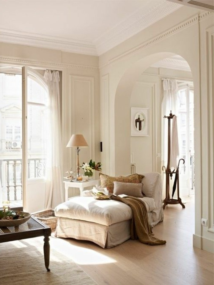 fainting couch in cream, with beige cushions, inside a room with cream walls, an open terrace door, and an archway detail