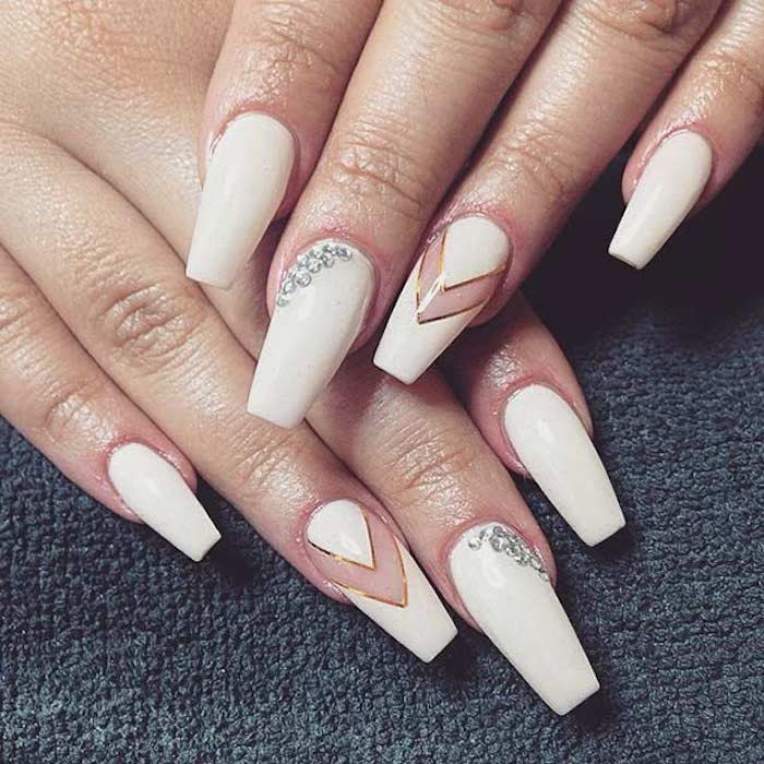 off-white nail polish, on long nails, decorated with rhinestones, clear details and thin gold stripes, ballerina nail shape, on two hands