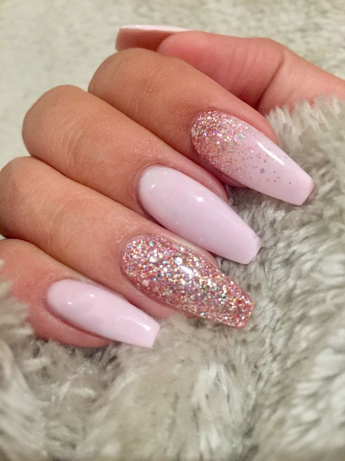 squoval nails in baby pink, decorated with pink glitter, and attached to a hand, gripping a light grey, fur-like fabric