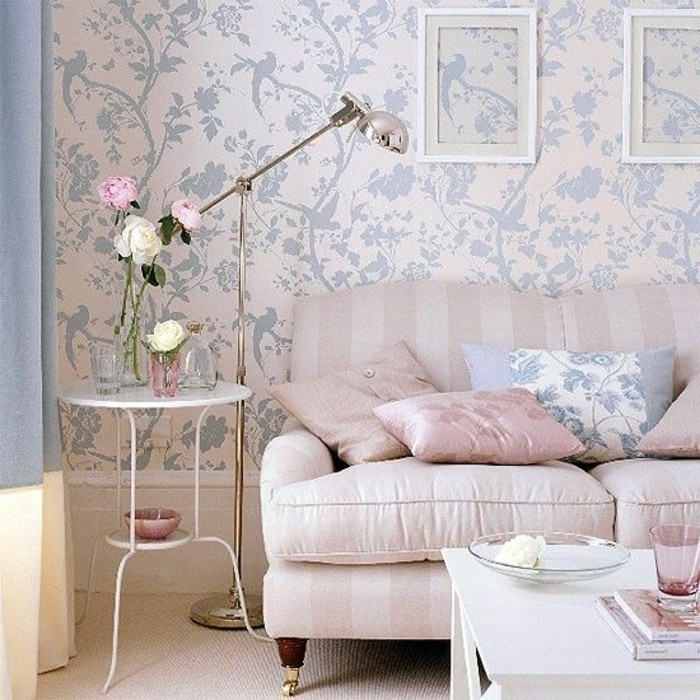 baby pink striped sofa, with matching pastel pink cushions, and one pale blue cushion, inside a room with light pink, and blue wallpaper, and two white coffee tables, in different sizes