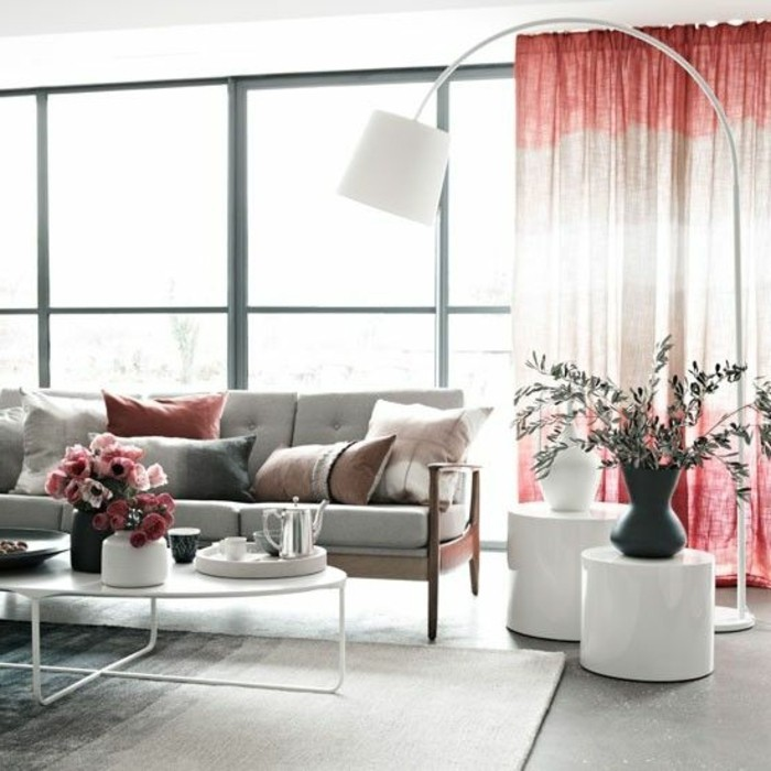 tall lamp in white, near two white stands, with grey and white vases, room setup ideas, pale grey sofa, with several cushions, and a white coffee table, with pink flowers
