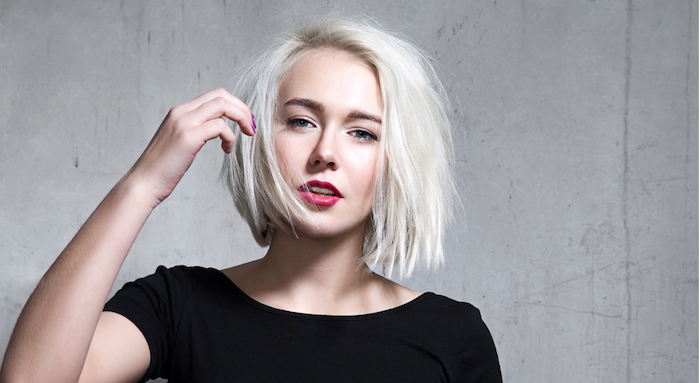 short haircuts for fine hair, platinum blonde messy bob, with deep side part, worn by woman in black t-shirt, with red lipstick