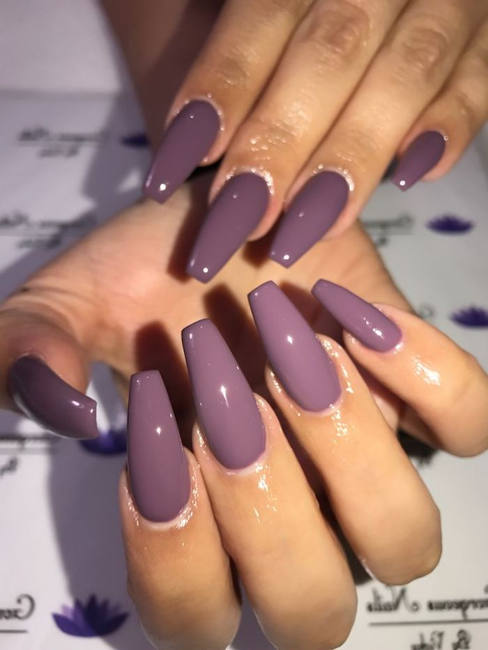 milky purple nail polish, glossy and smooth, on long coffin acrylic nails, attached to two hands, resting on a white, patterned background