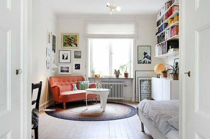 brick red settee, inside a white room, with a round multicolored rug, and a small modern coffee table, living room furniture for small spaces, book shelves and a bed