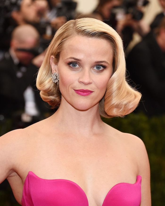 retro blonde curls, styled on a long bob, with deep side part, short hairstyles for fine hair, worn by reese witherspoon, in a hot pink strapless top, with matching lipstick