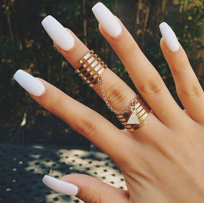 chain linking two golden rings, worn on the middle finger of a hand, with long coffin nails, painted in pure white nail polish