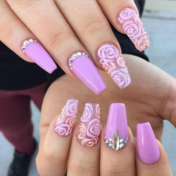 pink nails with rhinestones, and clear nails, decorated with rose drawings, in different shades of pink, with а ballerina nail shape, on two hands seen in close up