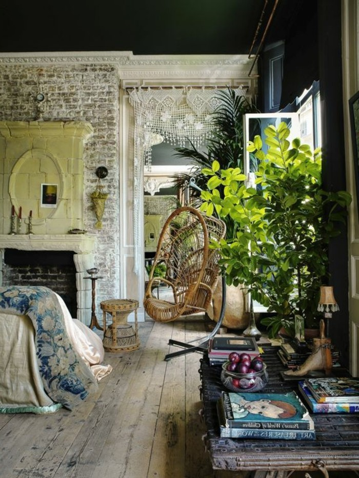 boho style rustic room, with a vintage and worn wooden floor, and shabby brick walls, large green indoor plants, books and decorations