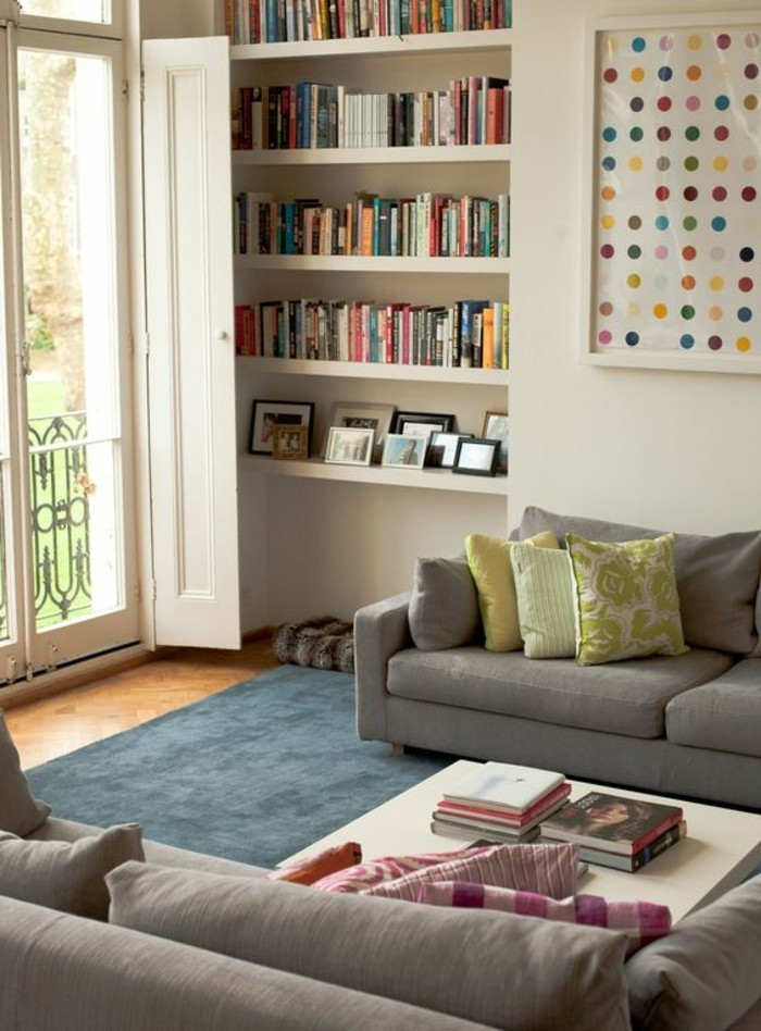 set of two pale grey sofas, with pink and yellow patterned cushions, a white coffee table, and white bookshelves, simple living room designs