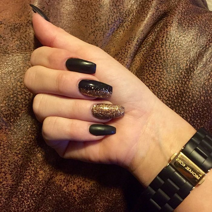 watch in black and gold, on the wrist of a hand with squoval nails, painted in black, and decorated with gold glitter