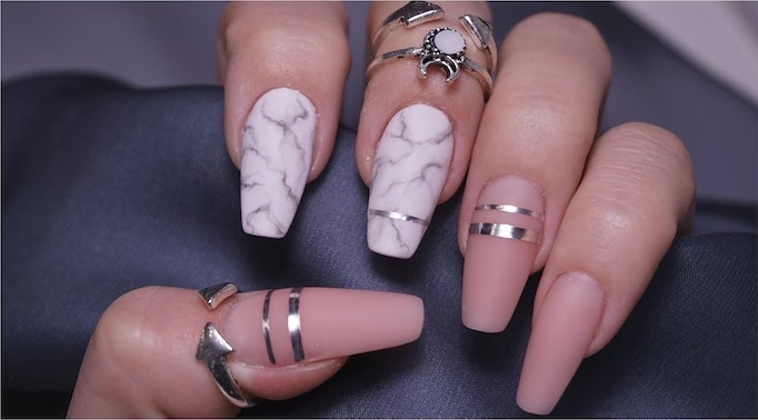 stripes made from a silver metallic substance, decorating the coffin nails of a hand, gripping a dark grey fabric, two of the nails are white, with marble pattern, white the other three are matte nude pink
