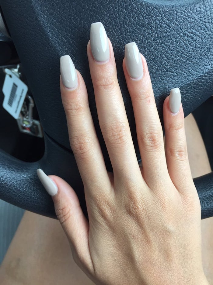 steering wheel in black, under a hand with long slender fingers, and nude coffin nails, in a milky ashen beige hue