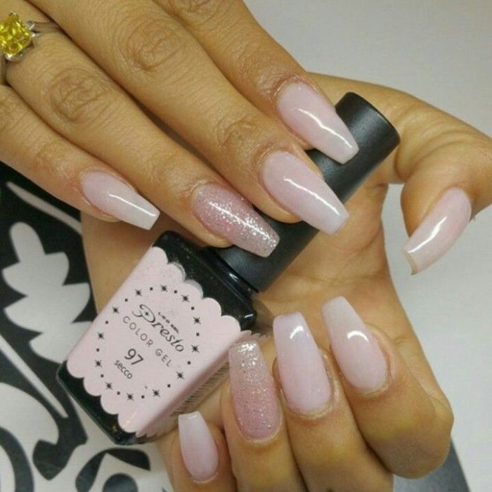 bottle of nail polish, in pale pink and black, held by two hands, with pink nude coffin nails, two of the nails are decorated with pink glitter