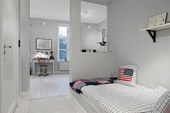 us flag cushion, on a bed with checkered cover, inside a room with pale grey walls, and a single bookshelf, room setup ideas, white desk with a brown chair in the background