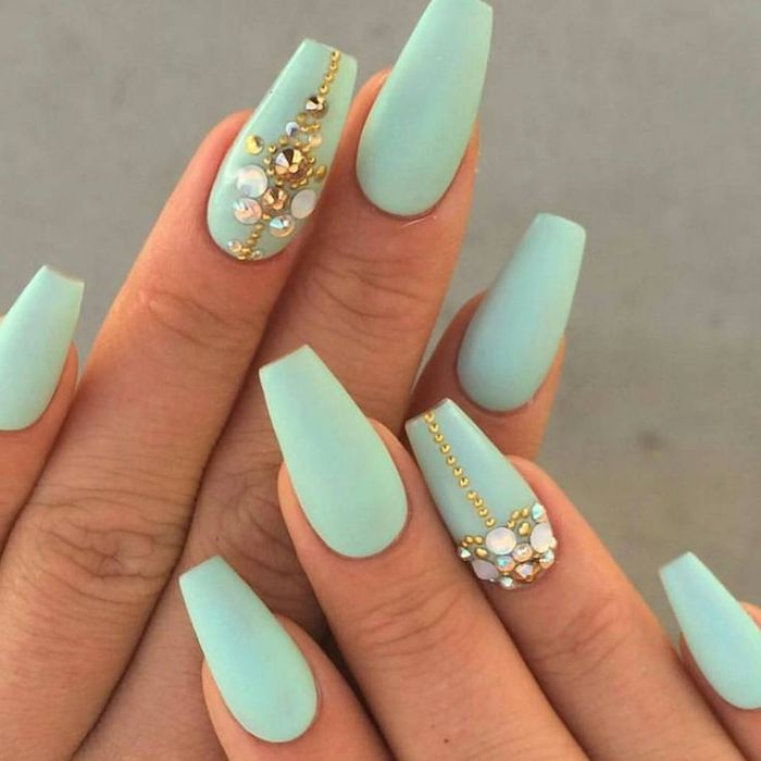 small gold beads, and iridescent rhinestones, on the ring finger nails, of two hands, with coffin manicure, painted in a pale turquoise color