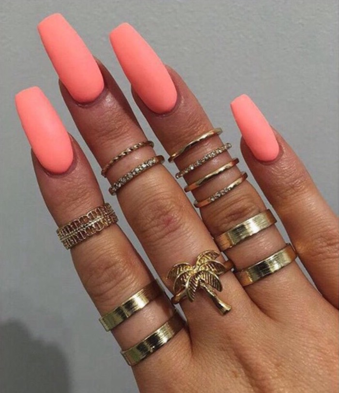 neon peach pink nail polish, on long coffin nails, attached to a tan hand, with twelve different golden rings, on a grey background