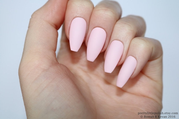 plain pale pink nail polish, on matte coffin nails, attached to a pale hand, with folded fingers, seen in close up