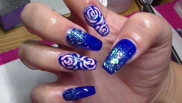 violet nail polish, decorated with pale pink and blue rose drawings, and blue iridescent glitter, on the long coffin acrylic nails, of a hand with folded fingers