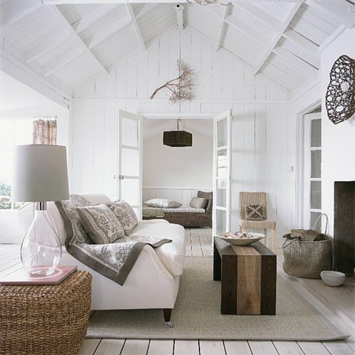 vaulted ceiling in white, inside a living room, with white wooden paneling, room design, light beige floor, with a beige rug, white sofa and wooden furniture