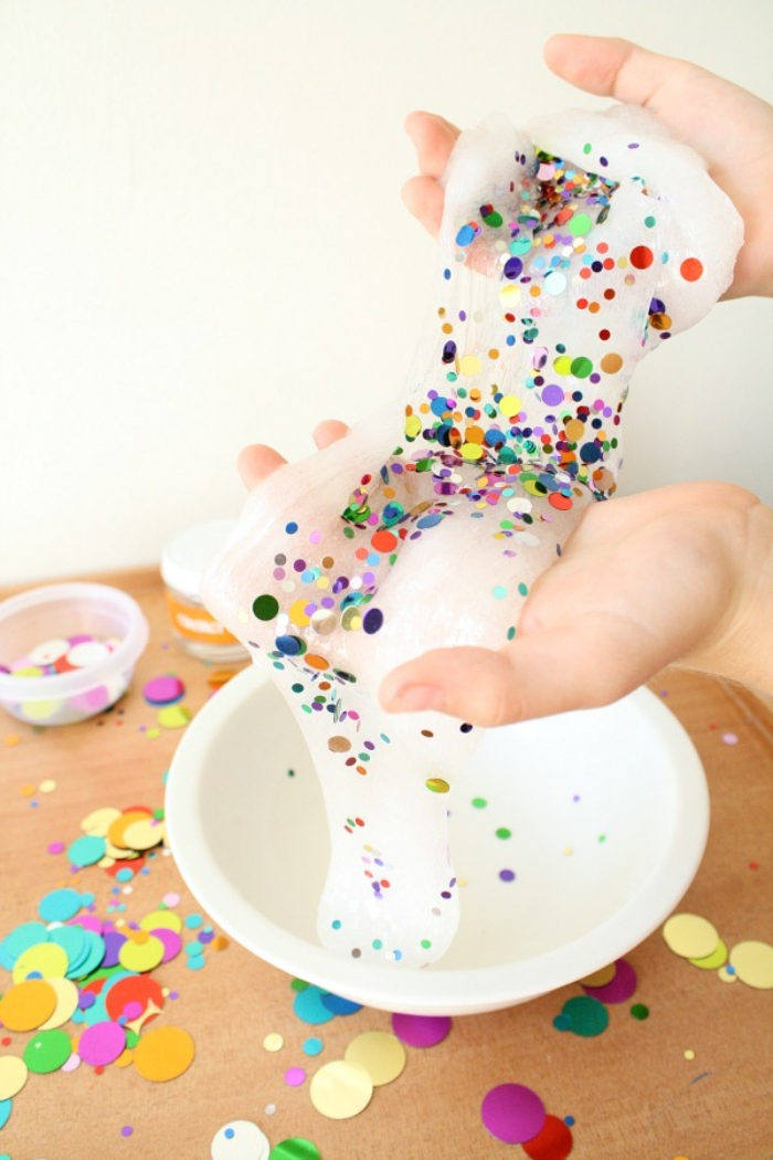 round confetti in different colors and sizes, decorating a piece of white slime, held in two pale hands, how to make slime with shaving cream, more confetti strewn about