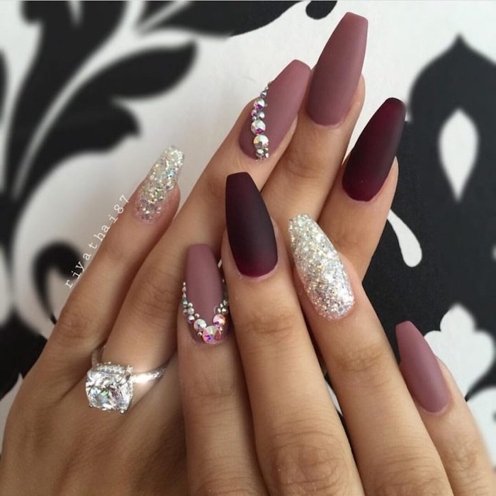 dark maroon and ashen rose matte nail polish, decorated with silver glitter and rhinestones, on the long nails of two hands