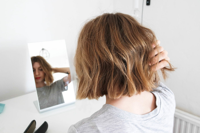 young woman looking at her reflection in a mirror, placed on a white desk, near some straightening irons, short haircuts for fine hair, light chestnut brown wavy bob