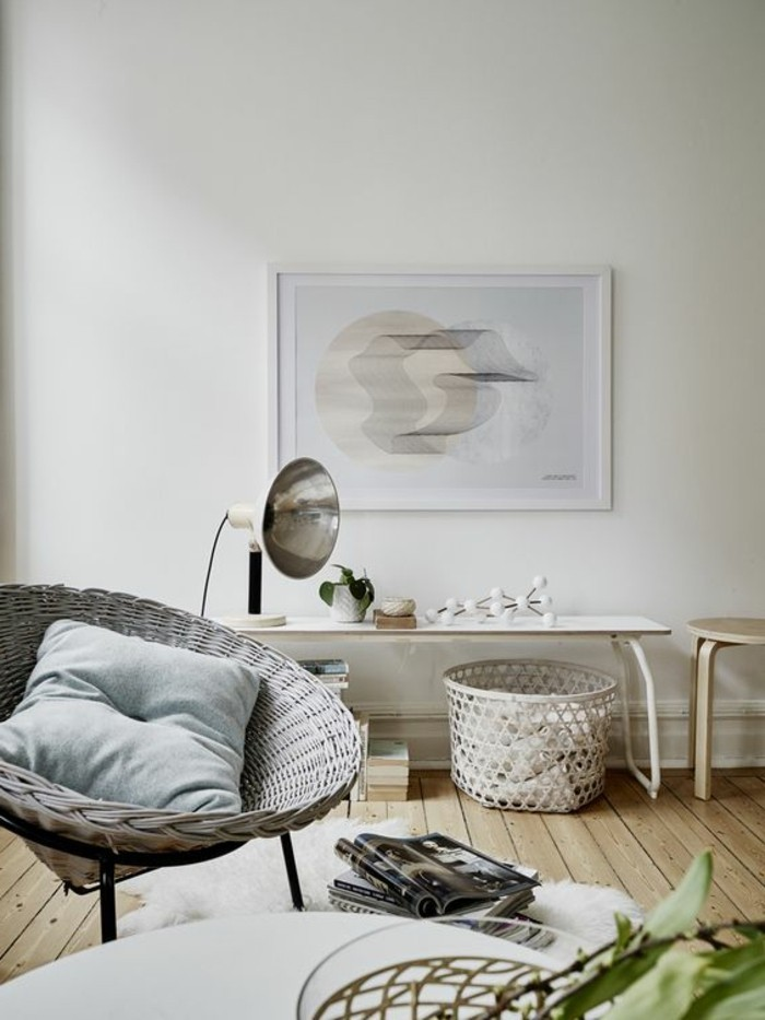 abstract painting mounted on a white wall, inside a room with pale, beige wooden floor, containing an off-white wicker chair, a white desk and a stool