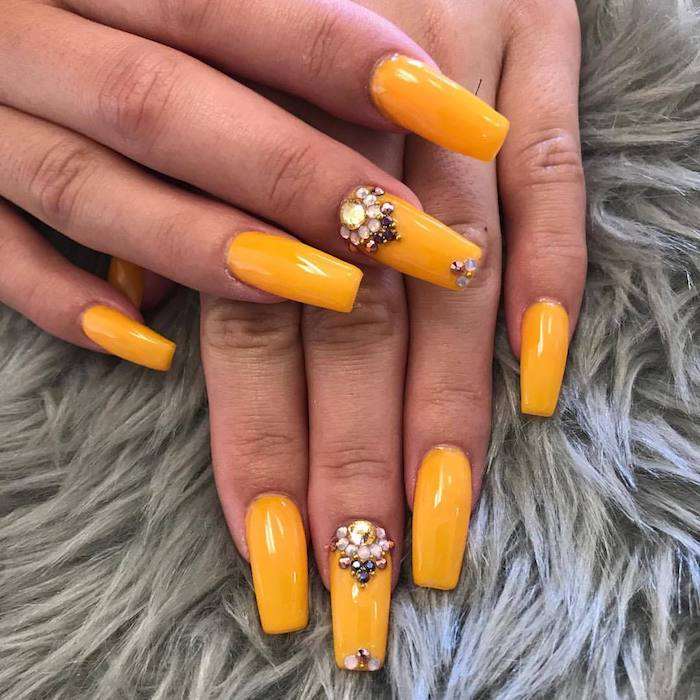burnt yellow nail polish, decorated with rhinestones, on the long coffin nails, of two hands, resting on a fur-like, pale grey surface