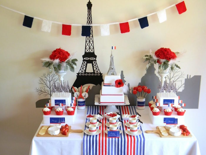 flags in black white and red, hung above a table with a white red and blue tablecloth, containing various French sweets, 2 bouquets of red roses, a three layered cake, 60th birthday ideas, two cheese boards, and an eiffel tower mural