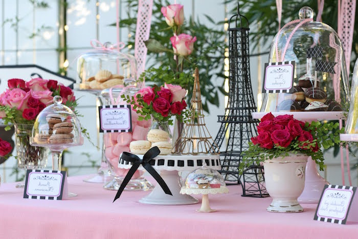 eiffel tower decorations, and several bouquets of red and pink roses, on a table with a pale pink tablecloth, containing macarons and various other kinds of sweets, French themed party, 60th birthday ideas