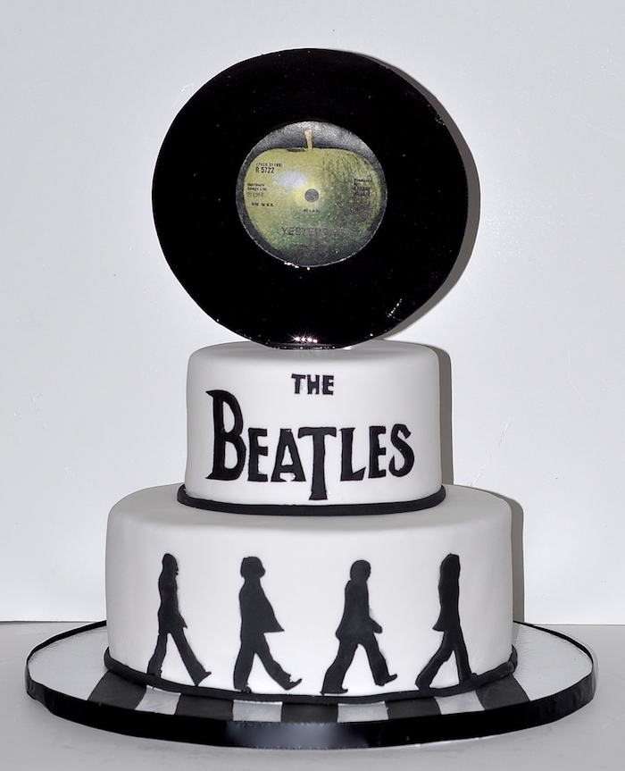 the beatles crossing abbey road, painted in black on a white cake, topped with a vinyl record, with the drawing of a green apple