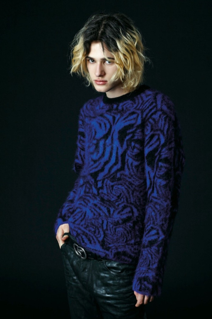oversized fluffy sweater, electric blue with black animal print, worn by a young man, 90s outfit ideas, with black leather trousers, and shoulder length curly hair
