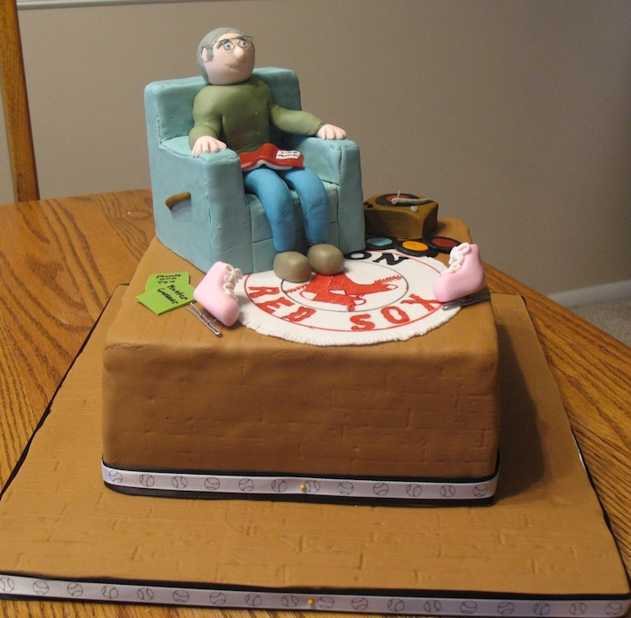 60th birthday party ideas for men, fondant figurine of a smiling man, sitting in a blue armchair, over a red sox logo carpet, surrounded by a vintage record player, and ice skates