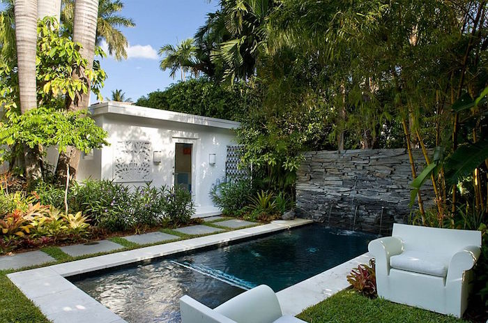 palm trees and various shrubs, in a garden with a small white shed, and a rectangular swimming pool, cool backyards, two white armchairs