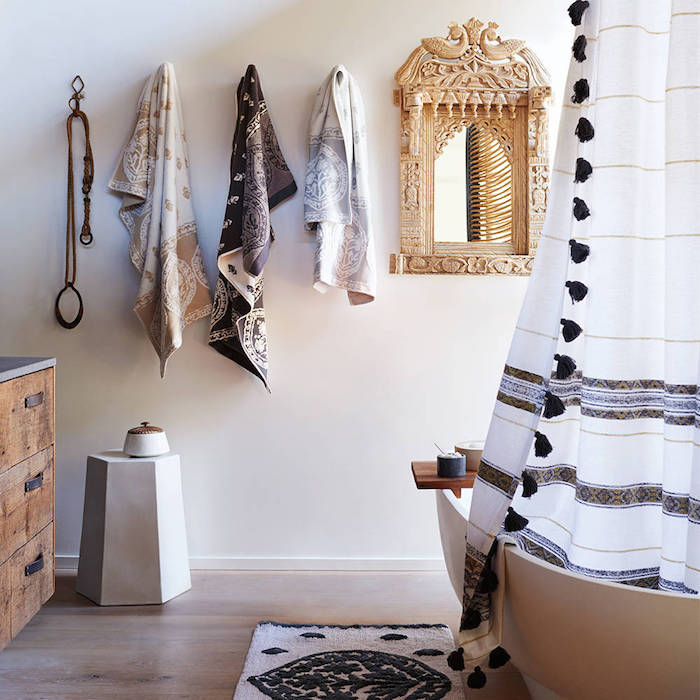 three towels with beige, brown and grey patterns, hanging on a white wall, near a mirror in an ornate frame, and a white bathtub, diy bathroom decoration