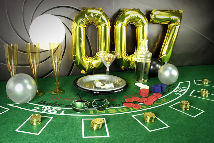 gambling table with chips, gold coins and three yellow champagne flutes, metallic balloons shaped like the number 007, 60th birthday party ideas for men, james bond theme