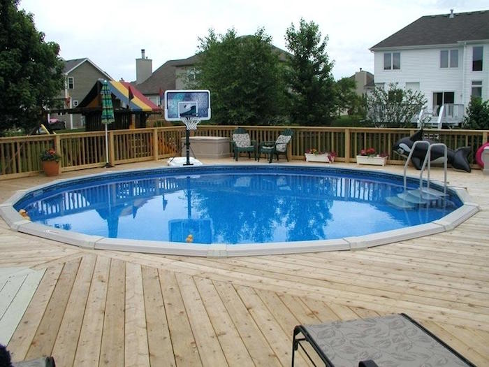 inflatable toy and a basketball net, near a circular pool, in a yard, covered by wooden planks, pool patio ideas, neighborhood houses in the background